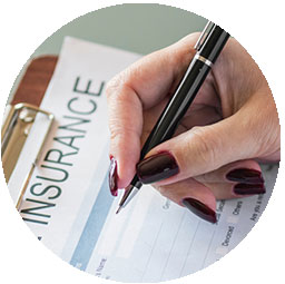 woman holding a pen filling out an insurance form